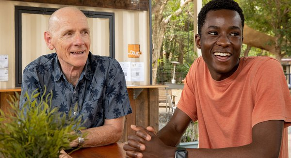 two men smiling at cafe