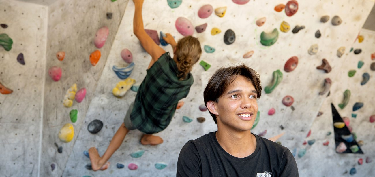young man with woman on rock wall